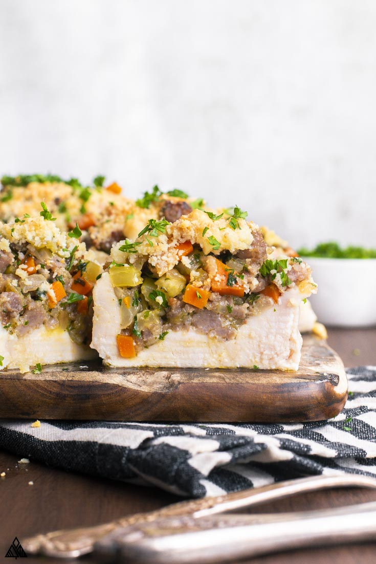 Closer look of sliced stuffed chicken breast with stuffing on a cutting board