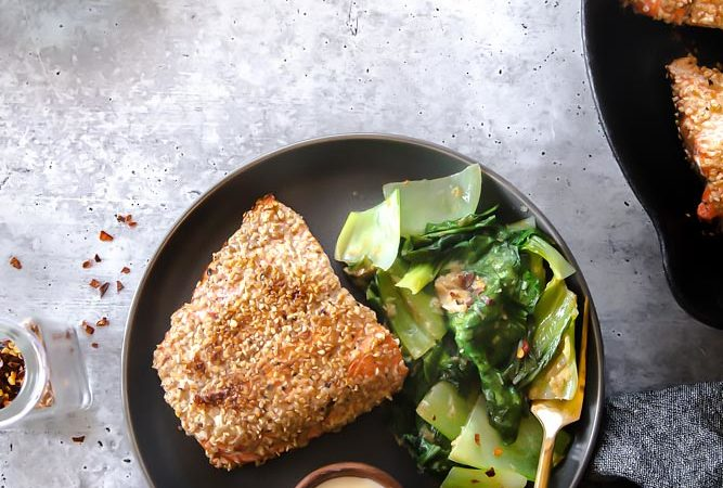 Top view of breaded salmon on a plate with vegetable sided and a fork