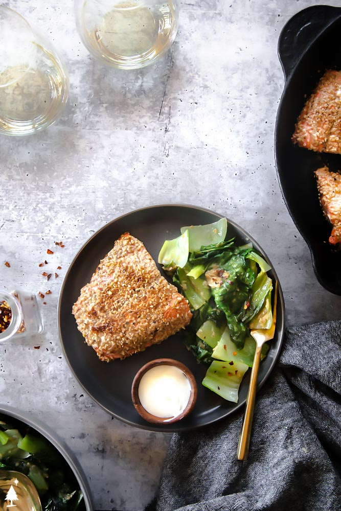 Top view of breaded salmon on a plate with vegetable sides and a fork