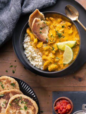 top view of indian chicken curry in a bowl with low carb naan