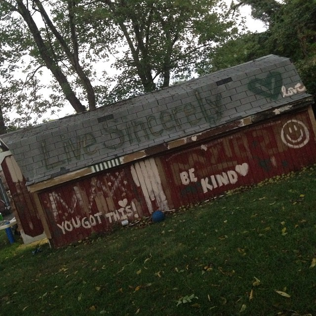 "September 2015: ""Some punks (aka, us) graffitied our shed today, with the same colors that rooms of our house have been painted in the past. At least their messages weren't *too* rude. (Here's hoping the landscapers don't back out of coming to demo the shed sometime soon!)"""