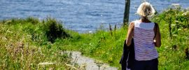 Woman walking alone along path by the sea