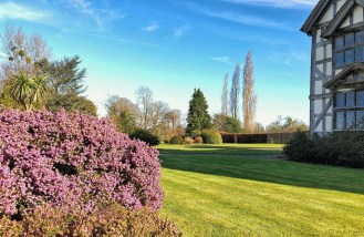 Early colour at in garden and lawn of country house