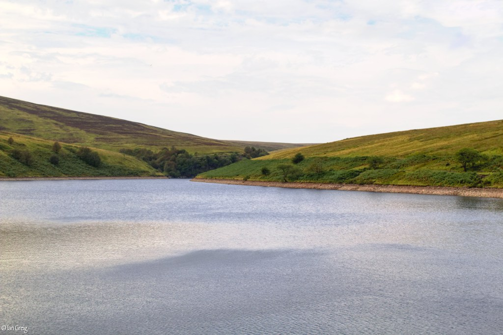 Reservoir scene with an expanse of blue water surrounded by mountain slopes
