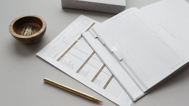 Documents including a personal budget spread across a table