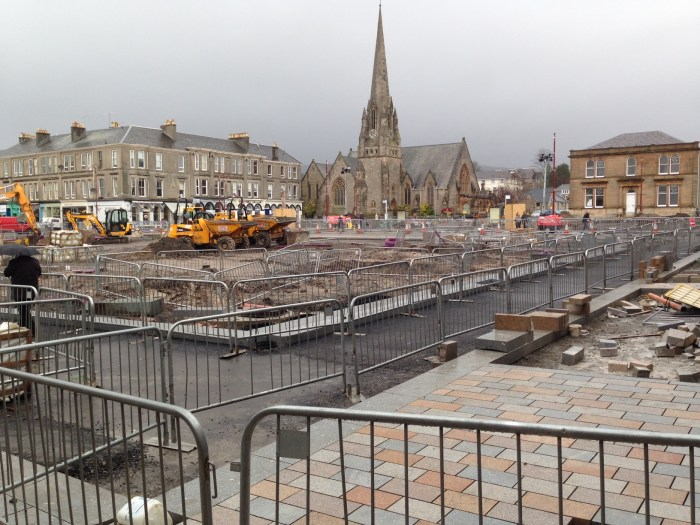 Barriers dominate Colquhoun Square, but the new paving is starting to appear.