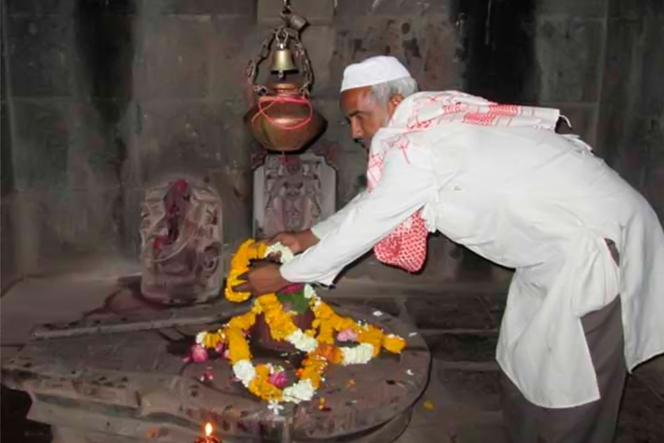 Muslim caretaker offers garland on Shivalinga