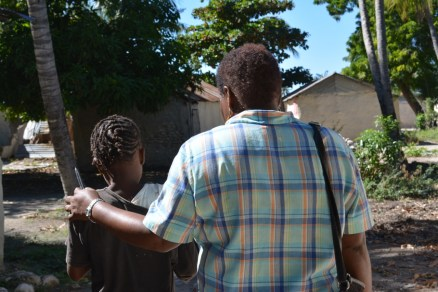 Yvette Michaud, a member of the executive committee of FONDAMA, an advocacy network in Haiti, walks with Esthelande, 10, in the girl's community.