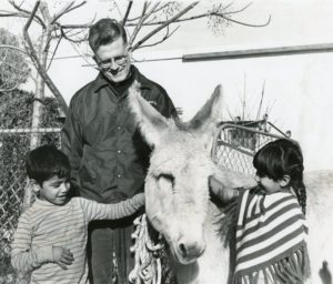 Fr. Thomas with two children and a donkey.