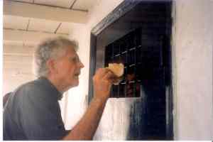 Fr Rick giving bread to prisoners in cell