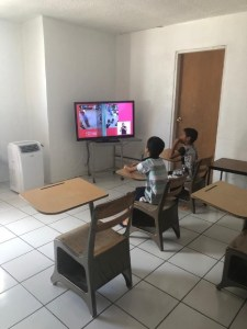 two boys watching class on TV