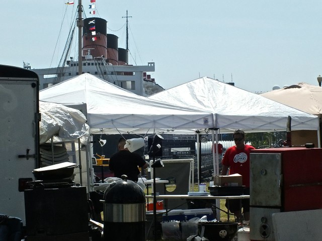 Setting up the BBQ booth with the Queen Mary in back. Photo by Ed Simon for The Los Angeles Beat.