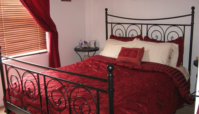 Traditional red and cream colored bedding on an IKEA NORESUND bed
