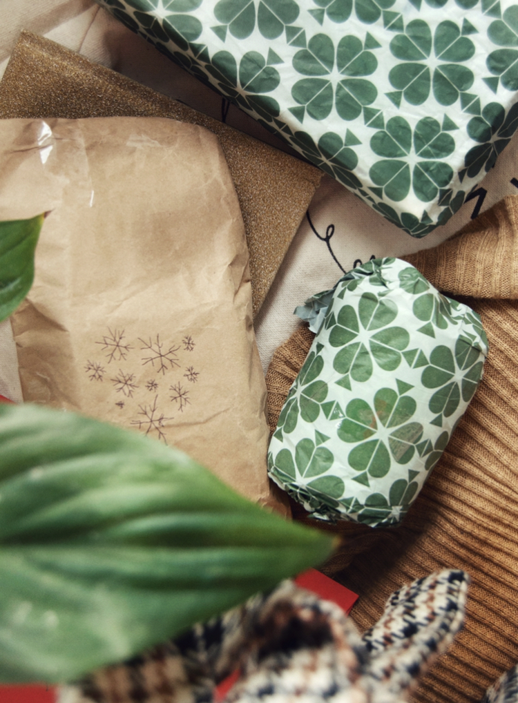 Flatlay of presents wrapped in paper wrapping paper, as it is a little more sustainable than plastic wrapping.