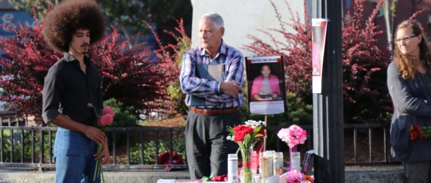 Leonard Perry prepares to lay flowers at a vigil for David Josiah Lawson, August 15, Arcata Plaza.   Photo by Curran Daly