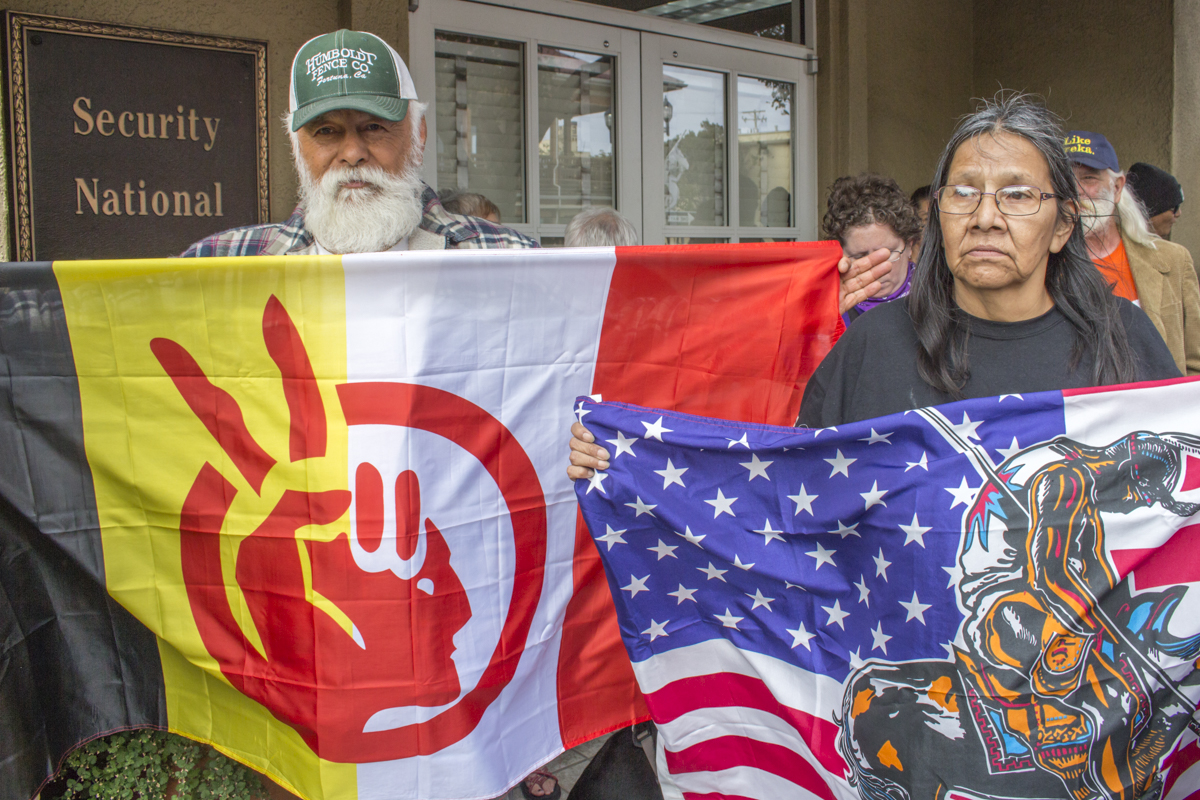 Left to right, Ambrose Arellana holds the American Indian Movement (AIM) Flag while family member Rose Pepetone holds a Native American flag.   Photo by Ian Thompson