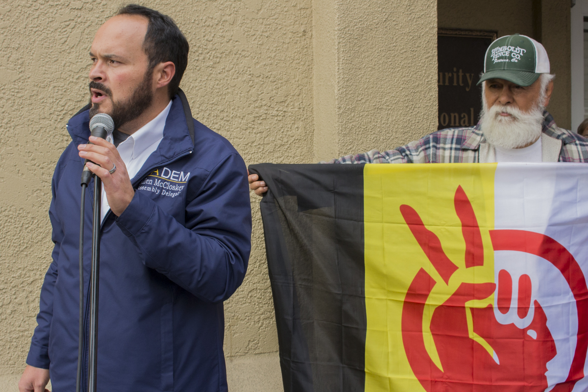 Left to right- California Democratic assembly delegate Allen McLoskey talking to crowd while Ambrose Arellana holds American Indian Movement flag.   Photo by Ian Thompson