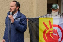 Left to right- California Democratic assembly delegate Allen McLoskey talking to crowd while Ambrose Arellana holds American Indian Movement flag. | Photo by Ian Thompson