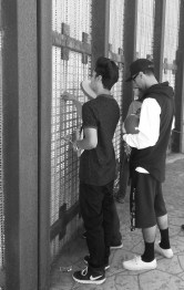 A young man tries to fit his pinky through to touch someone on the other side of the fence. | Photo by Kelly Bessem