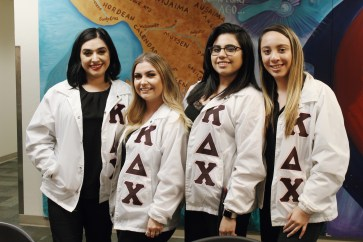 "Sisters of Kappa Delta Chi pose for a photo in their letters. Sweatshirts, shirts and jackets that feature an organization's name in the Greek alphabet are referred to as ""letters."" Letters are a way for individual members to showing spirit and pride for their organizations."