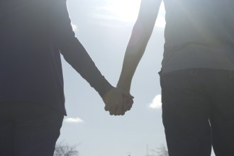 a couple holding hands walking into the sunlight