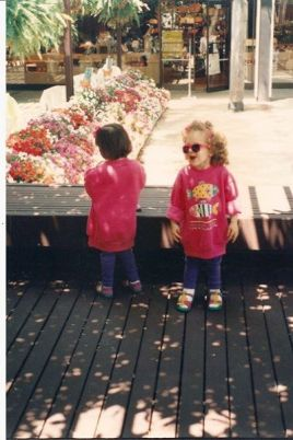Standing next to my twin sister; the swelling in my right foot was visible from a young age.