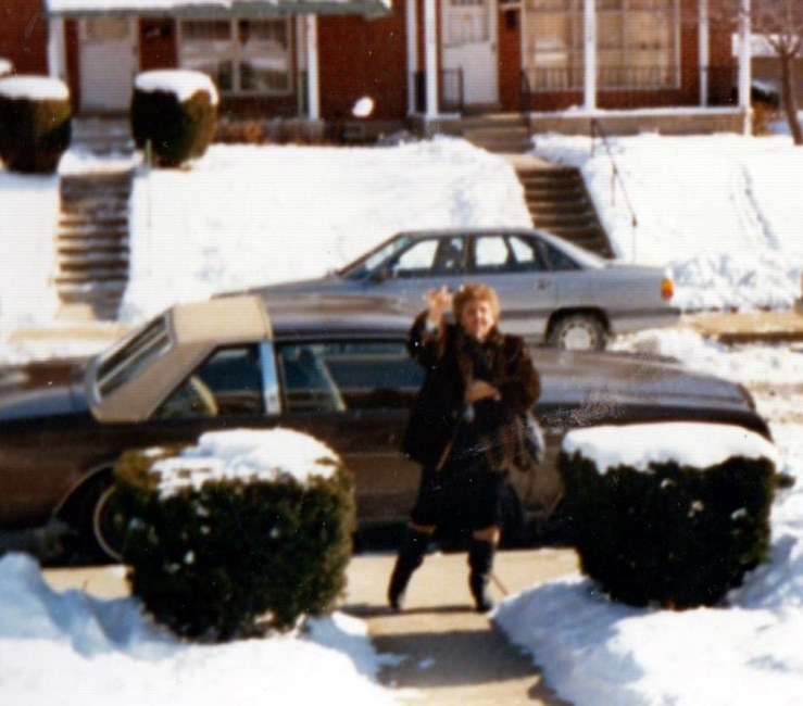 Alexa's grandmother, Phyllis Della-Rocca, waves from the sidewalk in front of her parked car.