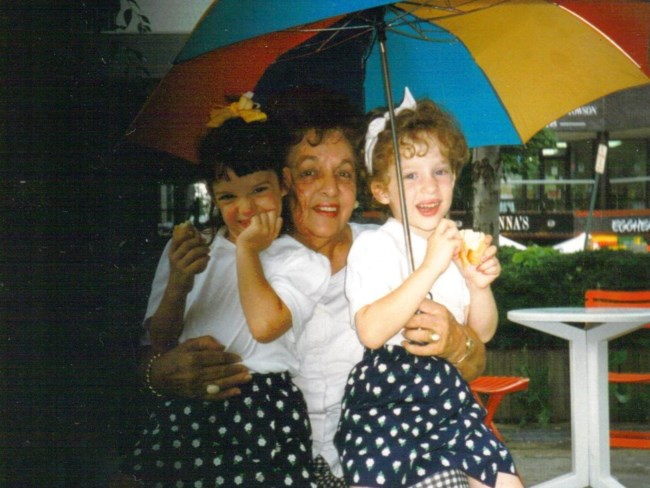 Alexa and her sister, Breanna, sit with their grandmother, Phyllis Della-Rocca, under a colorful umbrella.