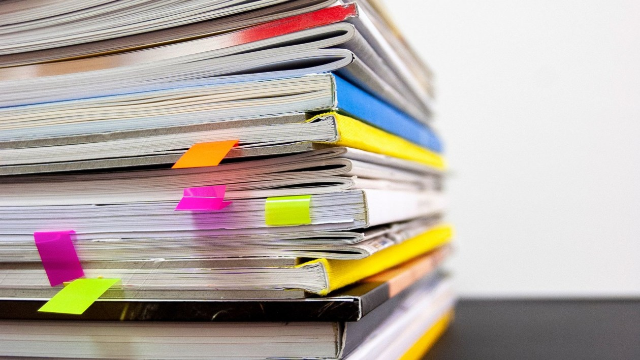 A stack of magazines with colorful flags to mark pages of interest.