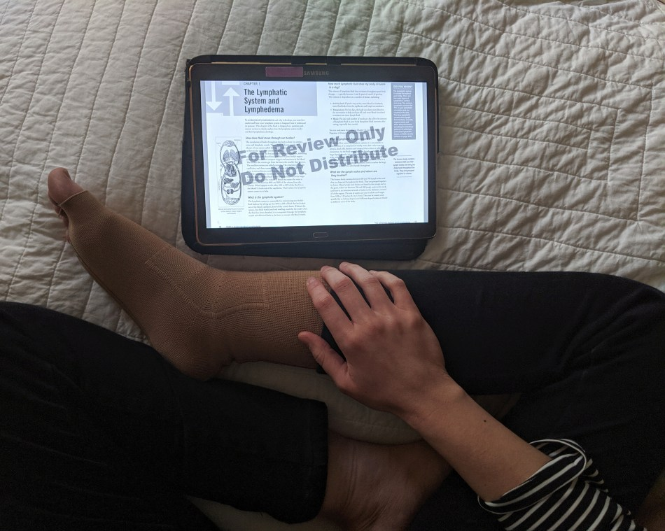 Alexa reads the e-book on her tablet while sitting on her bed.