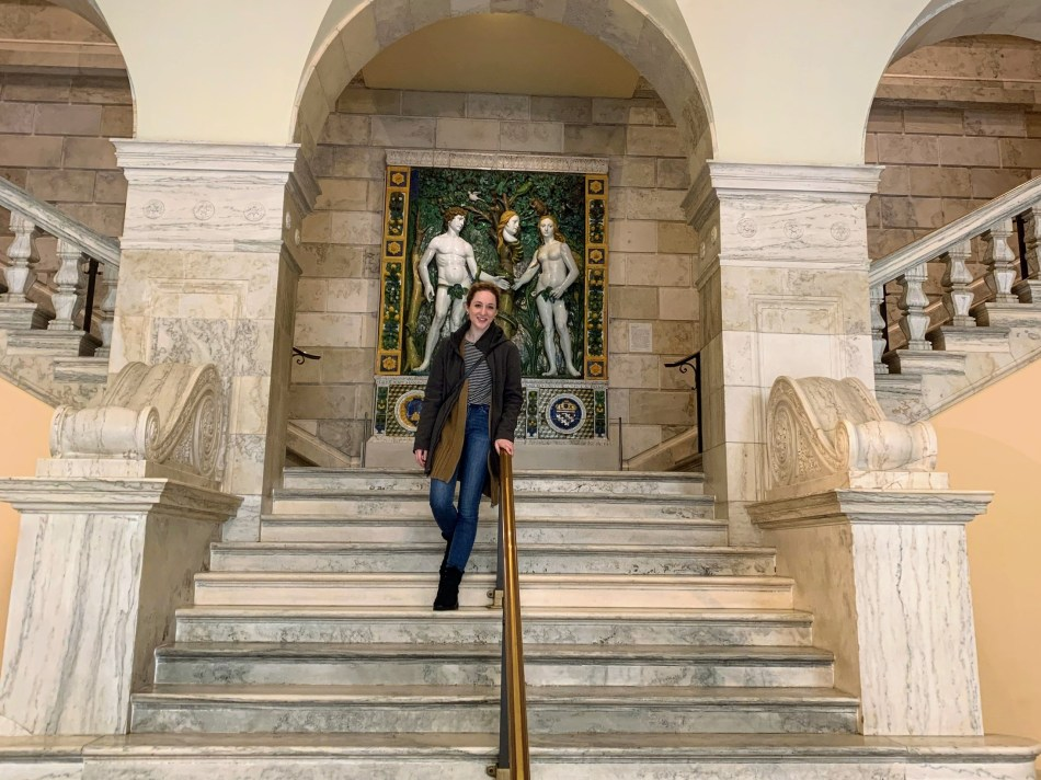 Alexa stands on the steps inside of the Walters Art Museum.