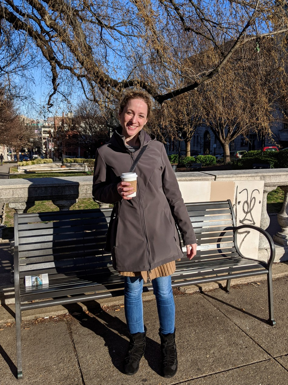 Alexa stands outside, smiling, while holding a cup of coffee.