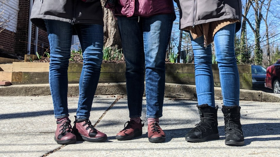Three women stand together, wearing Pandere shoes.