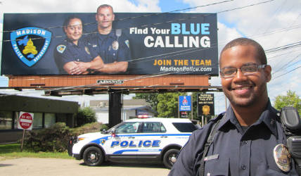 Officer Tyrone Williams poses in front of new billboard campaign for local recruitment. Photo by Brianna Rae