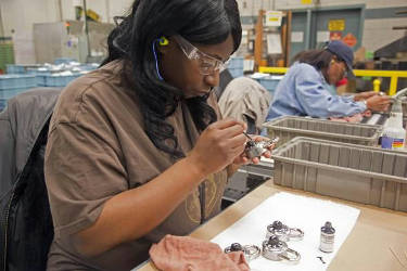 Delisa Scales touches up locks inside the Master Lock company's facilities in Milwaukee. One University of Michigan economist says the state's economic growth hinges on the manufacturing sector. AP Photo/Jeffrey Phelps