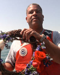 Erik Denson holds a wreath he brought aboard the dive boat. He asked his fellow scuba divers to say a few words to commemorate the Tuskegee Airmen. Photo courtesy of Urban News Service.