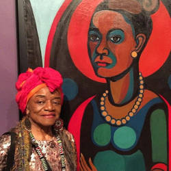 "Faith Ringgold standing with her ""Early Works #25: Self-Portrait,"" 1965, at the Brooklyn Museum. Photo by Robin Cembalest."