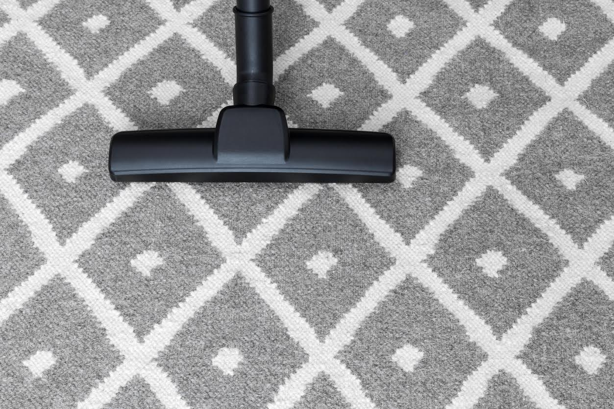 Housework. Vacuum cleaner on gray carpet.