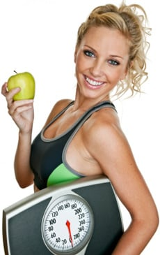 Fit Woman Holding a Scale And an Apple