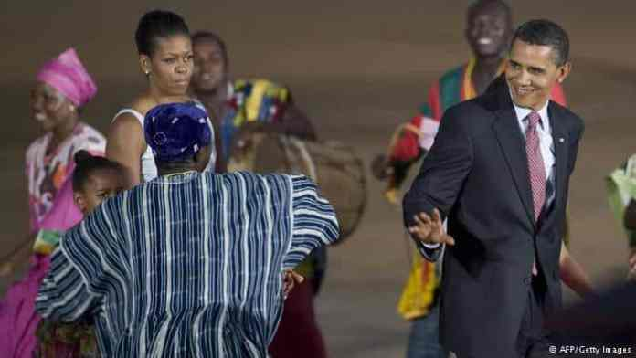 A smiling Obama walks by dancers, waving at them