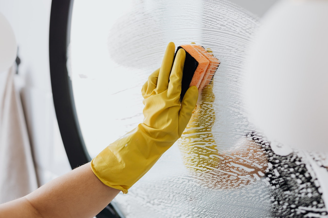 A person with yellow rubber gloves cleaning a mirror.