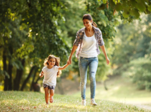 parent and child walking in woods