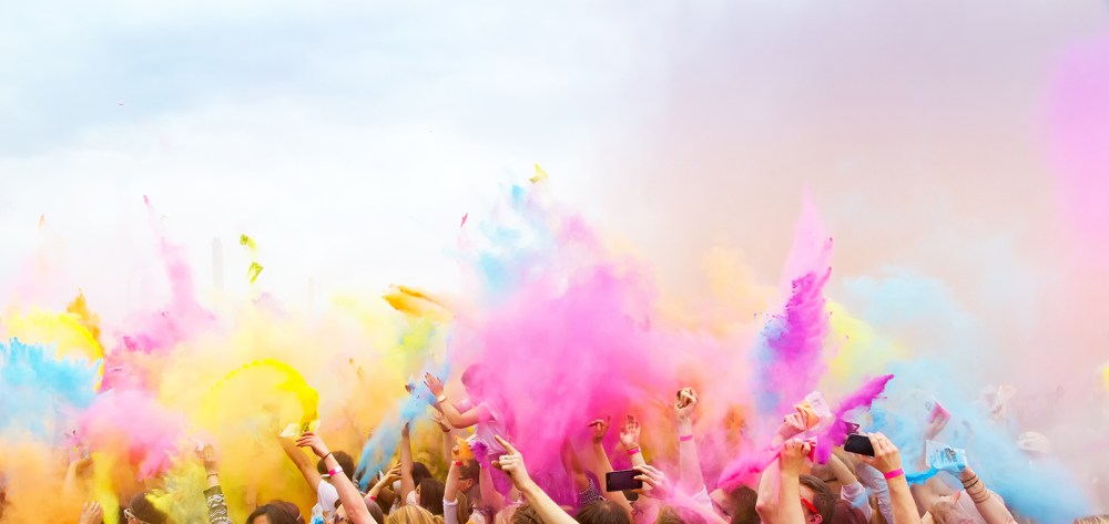 music festival audience dancing with multi-color smoke bombs celebrating diversity