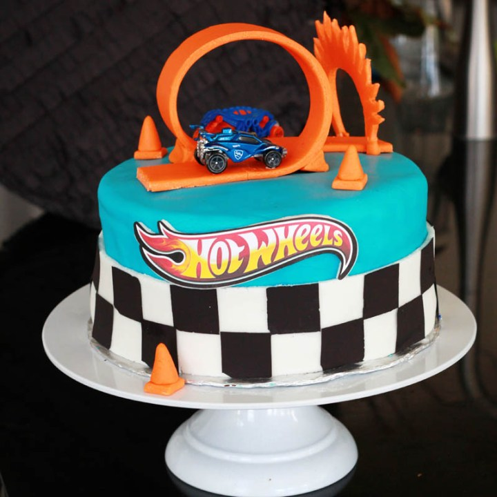 Hot Wheels Birthday party cake with blue fondant, black and white racing flag border, and orange loop track and ring of fire.