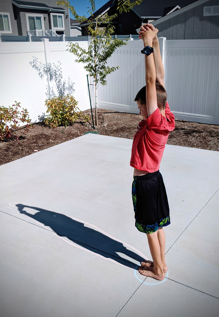 Boy making a shown on cement for human sundial experiment