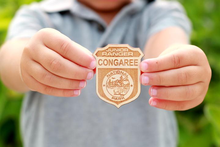boy holding junior ranger badge