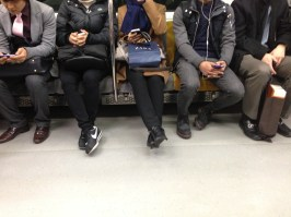 People using smartphones on a train