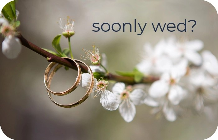 wedding rings hanging on flowering tree branch