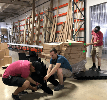 Employees build display racks for prefinished flooring samples