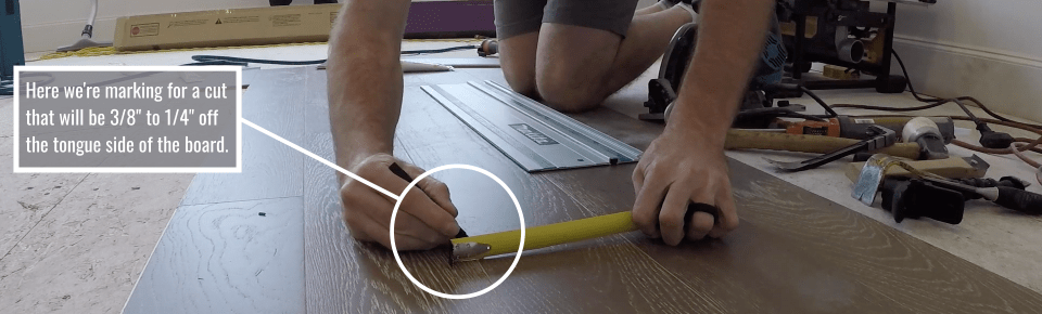 Video instructor making marks for repairing a hardwood floor board